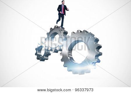 Smiling young businessman in suit running against metal cog and wheel connecting
