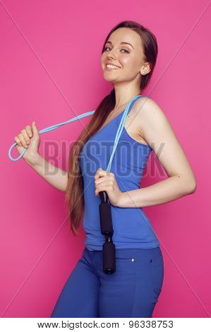 young happy slim girl with skipping rope on pink background