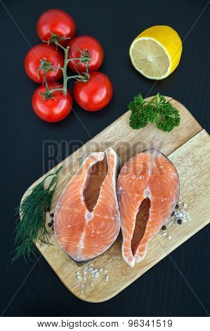 Salmon Steaks On A Wooden Board With Lemon And Tomato