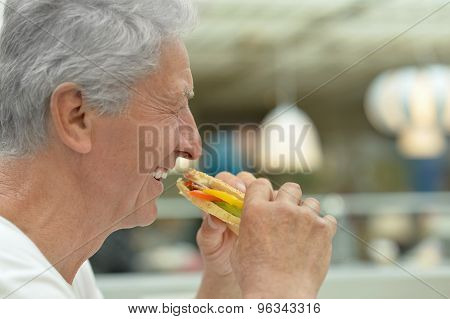 elderly man eating fast food