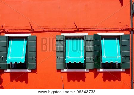 Three Windows With Blue Canopy In Burano On Red Orange Wall