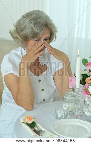Senior woman crying in room