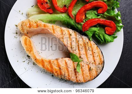 Tasty grilled salmon with salad pepper and lettuce on table close up