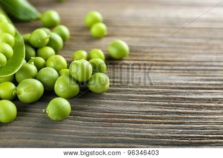 Fresh green peas on wooden table, closeup