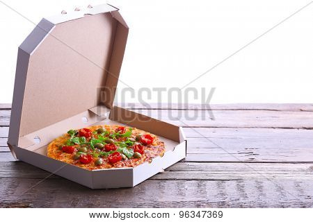 Pizza in box on wooden table isolated on white