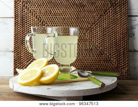 Still life with lemon juice and sliced lemons on wooden stand on wicker mat background