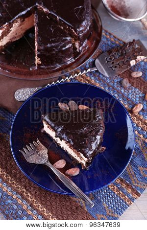 Delicious chocolate cake with icing in plate on table, closeup