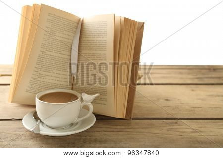 Still life with cup of coffee and book on wooden table, on white background