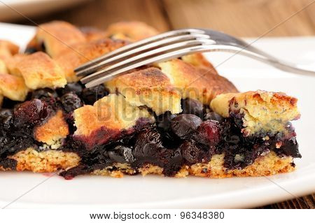Piece Of Juicy Homemade Lattice Pie With Whole Wild Blueberries In White Plate With Fork
