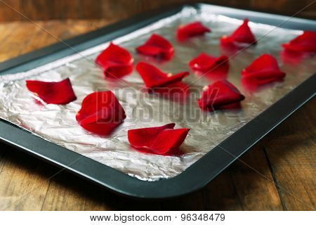 Roses petals on tray,on wooden background. Candied flowers concept