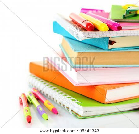 Stack of books and stationery isolated on white