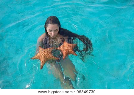 Wet Young Woman With Super Long Hair In Turquoise Sea Water Holding Two Big Starfish In Her Hands