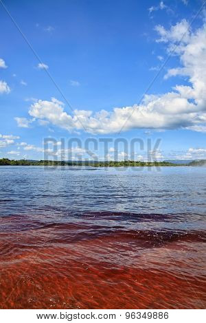 Red Lake Waters With Tropical Vegetation At Background - All Under Bright Blue Sky