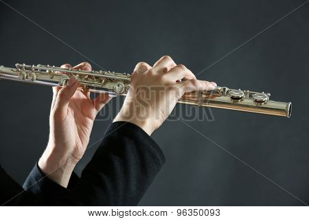 Musician playing flute on dark background