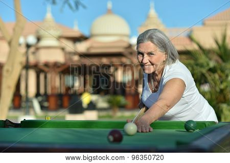 senior woman on vacation playing billiards