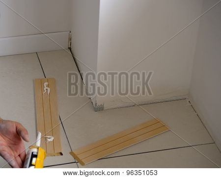 Carpenter on work putting wood skirting board
