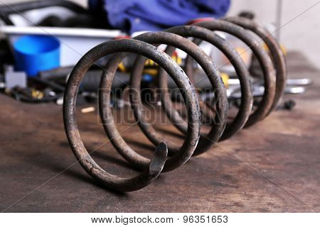 Large metal spring on workplace in garage