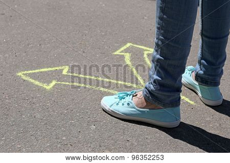 Female feet making choice on asphalt with drawing arrows, outdoors