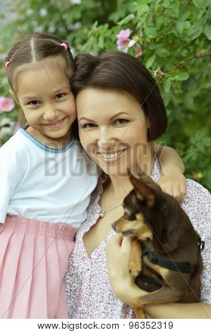 Girl and  mother in  park with dog