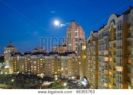 Moon In The Night Sky Over City.