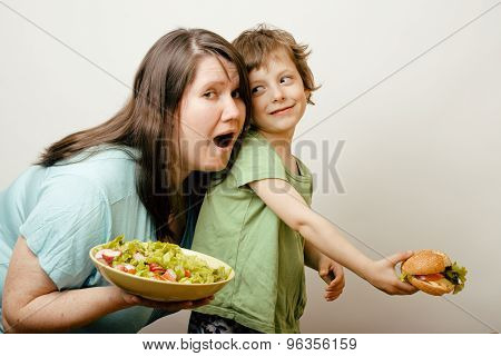 mature fat woman holding salad and little cute boy with hamburger teasing