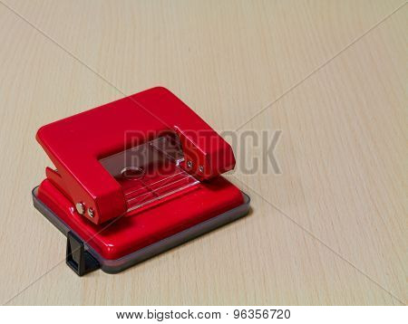 Red  paper hole puncher On Wooden Background.