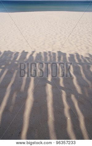 Shadow Of Wooden Shelter On The Beach Near
