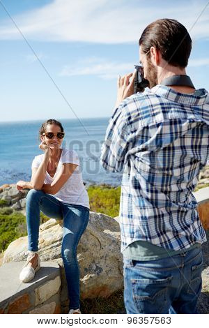 man taking pics of his girlfriend with a beautiful ocean background