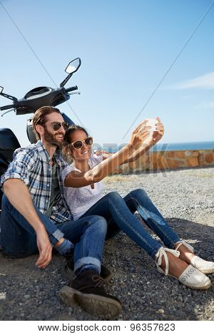 happy couple sitting near the ocean, against their scooter, taking a selfie on holiday
