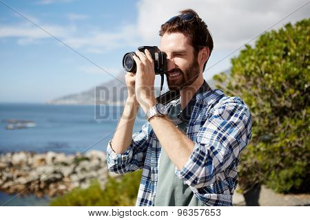 young, attractive caucasian man standing and taking pics of the ocean using a digital camera