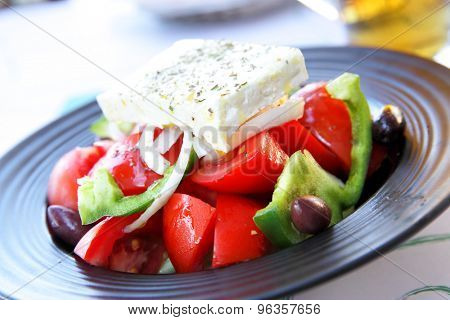 Right greek salad with one whole piece of feta cheese