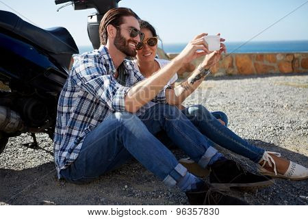 happy couple sitting near the ocean, against their scooter, taking a selfie