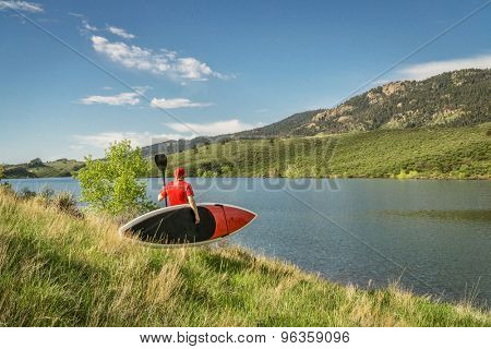 male paddler carrying a red stand up paddleboard and a paddle on a sunny summer day - Horsetooth Reservoir, Fort Collins, Colorado