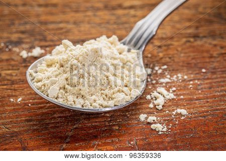 tablespoon of gluten free quinoa flour against rustic wood