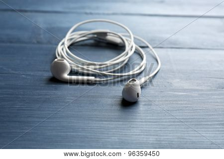White earphones on color wooden background