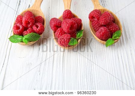 Fresh red raspberries in spoons on wooden background