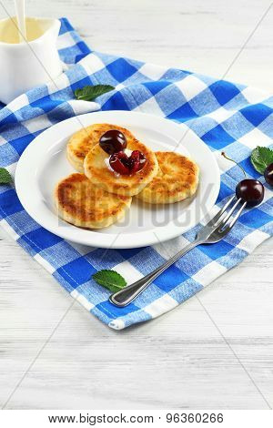 Fritters of cottage cheese with cherry and cream in plate on checkered napkin, closeup