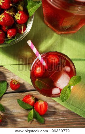 Full jug and glass of strawberry juice with berries on table close up