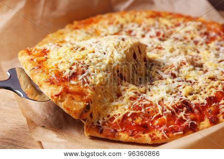 Cheese pizza on parchment with blade, closeup