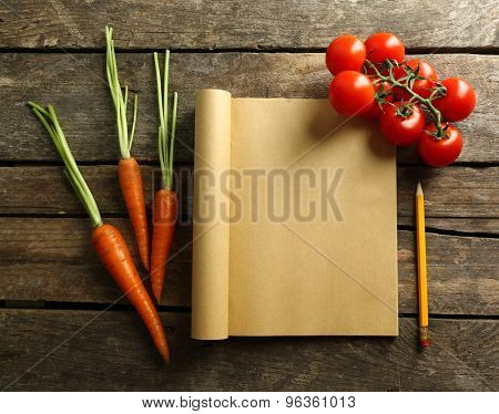 Open recipe book, vegetables on wooden background