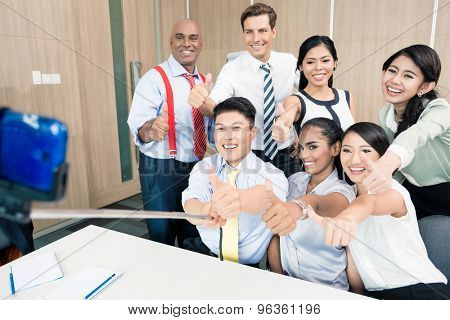 Business team taking picture with selfie stick