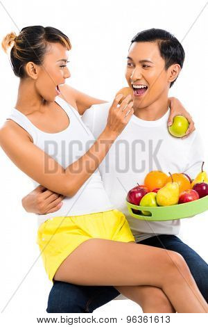 Asian couple eating fruit and living healthy