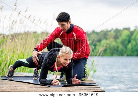Woman with personal trainer doing fitness push-up