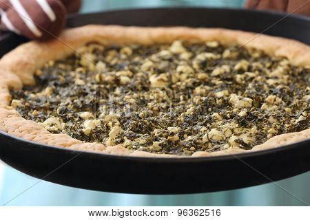 Woman holding open pie with spinach close up