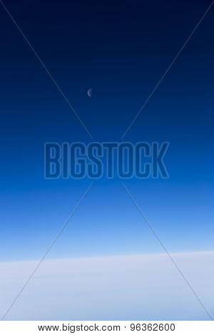 Moon in transparent sky over clouds