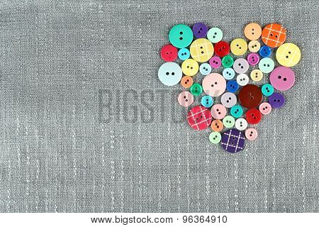 Colorful buttons in shape of heart on sackcloth background