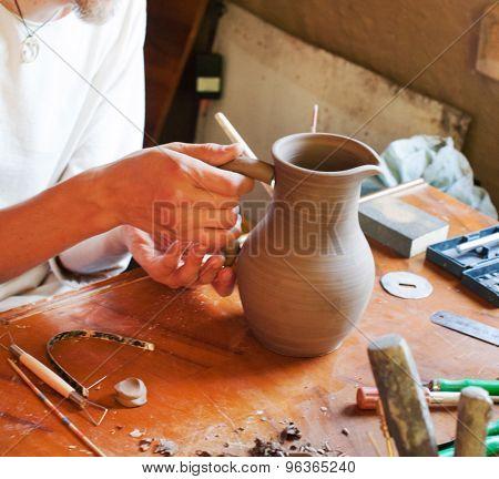 young men making clay pot