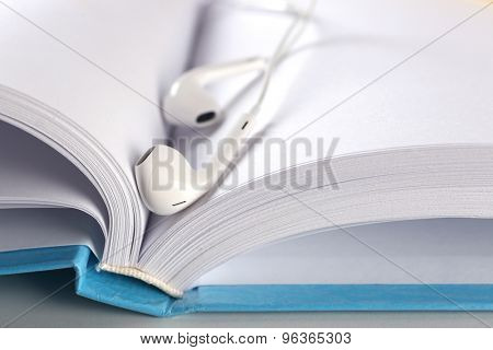 Earphones and book on table, closeup