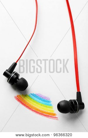 White earphones on white sheet of paper with colorful rainbow, closeup