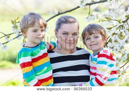Young Mother And Two Little Twins Boys Having Fun In Blooming Ga